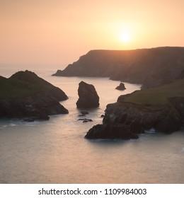 Beautiful colorful sunset landscape image of Kynance Cove on South Cornwall coast of England