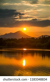 A beautiful, colorful sunset landscape with lake, mountain and forest. Natural evening scenery over the mountain lake in summer. Tatra mountains in Slovakia, Europe.