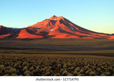 beautiful colorful sunset on the desert landscape of the area of san pedro de atacama in chile with a glowing mountain in the red sun light )