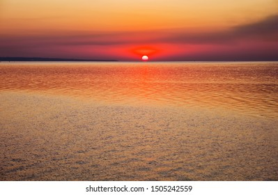 Beautiful colorful sunset on the sea coast. Nice scene with sunrise over water