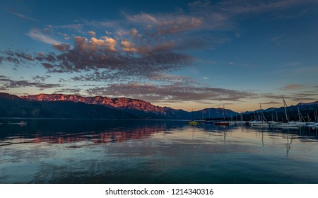 Beautiful colorful sunset over the Attersee lake with dramatic clouds and mountains in the background in Nußdorf, near Salzburg, Upper Austria