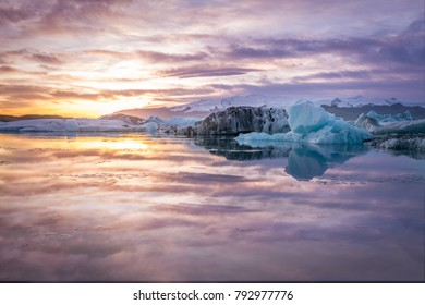Beautiful and colorful sunset over glacier at Jokulsarlon, lceland with purple sky and reflection over the water