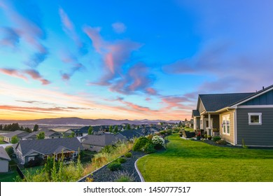 A beautiful, colorful sunset of pinks and aqua blues color the sky over a typical American subdivision on a hillside in Spokane, Washington.
