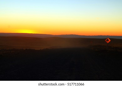 beautiful colorful sunset seen with a bright street sign shining next to a dusty road close to the plateau of San Pedro de Atacama in Chile