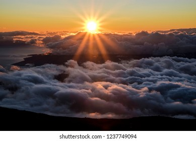 Beautiful Colorful Sunset Sky at Dusk with Sun Rays Coming Through Clouds from the Top of Haleakala Volcano in Maui Hawaii with Mountains in Background of Amazing Landscape in Island Paradise