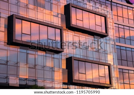 Beautiful colorful sunset sky reflecting off glass-covered building in Podgorica, capital of Montenegro.