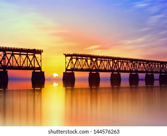 Beautiful colorful sunset or sunrise with broken bridge and cloudy sky. Taken at Bahia Honda state park in the Florida Keys, near famous tourist destination of Key West.