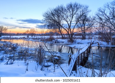 Beautiful colorful sunset at the winter frozen river. The sun has sat down for horizon, having painted the sky with bright paints.