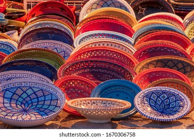 Beautiful colorful traditional ceramic items - plates and lamps at a market in Tunisia.