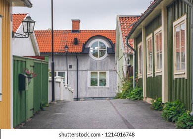 Beautiful colorful wooden buildings in Sigtuna, Sweden. View of color street with green, yellow houses, street lamps, orange tiled rooftops and round window in perspective. Cloudy sky on background.