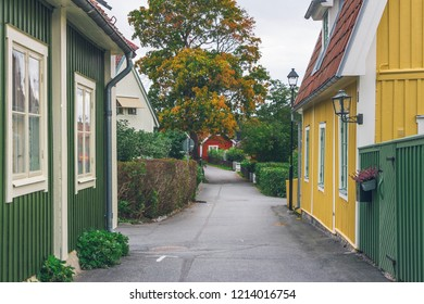 Beautiful colorful wooden buildings in Sigtuna, Sweden. View of color street with green, yellow houses, street lamps, orange tiled rooftops and red cottage in perspective. Cloudy sky on background.