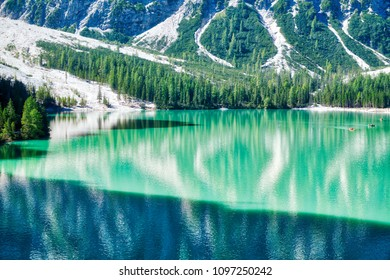 beautiful colors of Braies lake in summer season with sunny light, shadow and mountain Croda del Becco in background, Dolomites - Italy