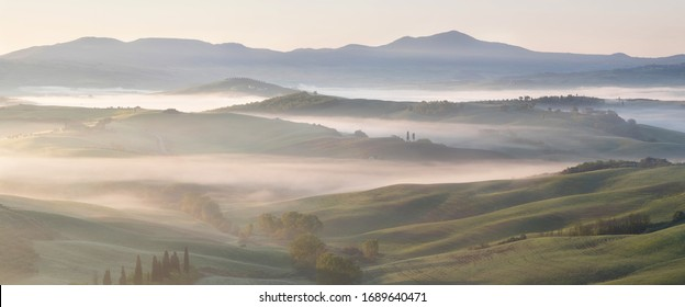 Beautiful colors of green spring panorama landscape of Tuscany. Most popular place in Italy. Green fields and blue sky and Cypress tree scenic road near Siena. Amazing foggy morning with sunshine