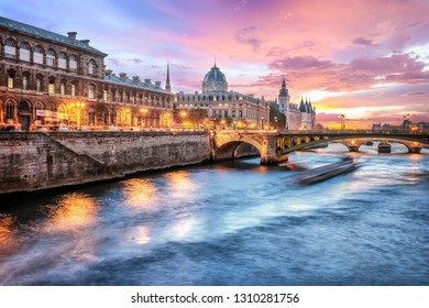 Beautiful colors of Napoleon Bridge at dusk with Seine river - Paris, France. Coral color sky.