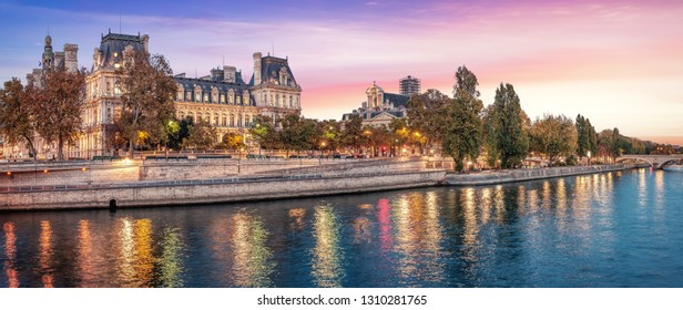Beautiful colors near Hotel de Ville at dusk with Seine river - Paris, France. Coral color sky.