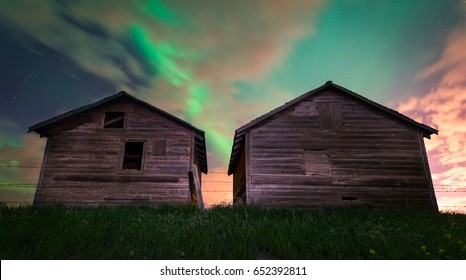 Beautiful colors of the Northern Lights (Aurora Borealis) behind old wooden rustic farm sheds in Alberta, Canada