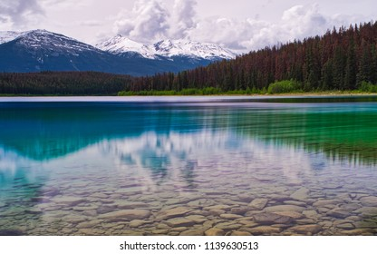 Beautiful colors in a perfect reflection of trees and mountains. Green and blue. Rocks in the foreground and a mountain in the back gives a great canvas. Lovely nature.