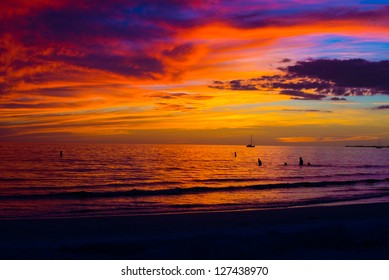 Beautiful colors of a winter sunset over the water of the Gulf of Mexico at Ft Myers Beach in Florida, placing the sailboat and swimmers in silhouette.