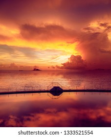 Beautiful colourful sky during sunset with reflection in the artificial pool. Dinart city, Brittany, France.