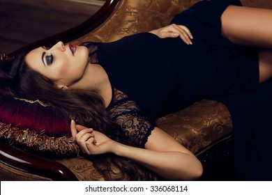 Beautiful come-hither woman in black evening dress laying down on the vintage sofa. Fashion make-up smoky eyes. Luxury. Sexuality. Seduction. Sensuality. Fashion model shooting. Italian style.