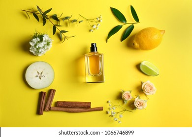 Beautiful composition with bottle of perfume, fruits and flowers on color background, flat lay