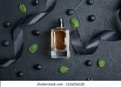Beautiful composition with bottle of perfume on dark background, flat lay