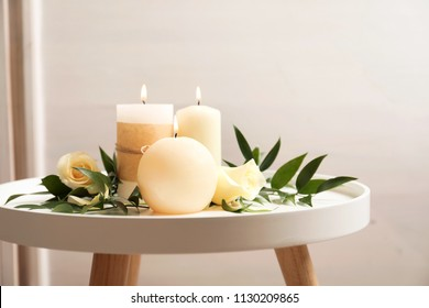 Beautiful composition with burning candles and flowers on table