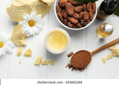 Beautiful composition with cocoa butter lotion on table