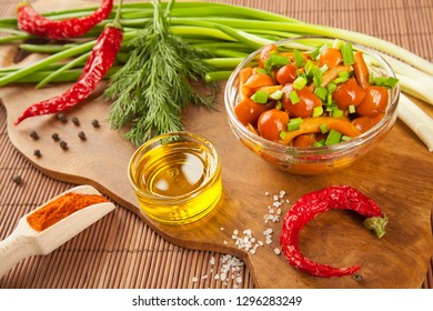 Beautiful composition of cooking ingredients on a wooden board: marinated honey agarics, fresh green onion and dill, chilli pepper, olive oil, spices