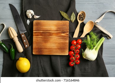 Beautiful composition with empty wooden board and vegetables on kitchen table. Cooking classes concept
