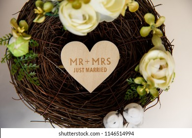 Beautiful composition in he form of bird's nest with floral decoration. Mr+Mrs. Just married. Ring box for wedding rings on white background.