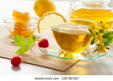 Beautiful composition of herbal tea served with honey, fresh raspberries and lemon on bamboo background