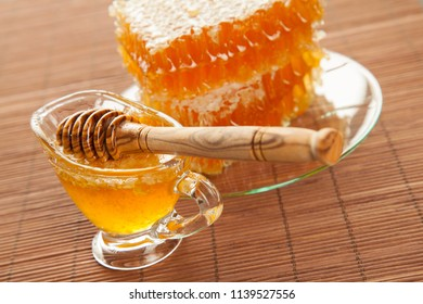 Beautiful composition of honeycombs and fresh honey in a glass bowl on bamboo background