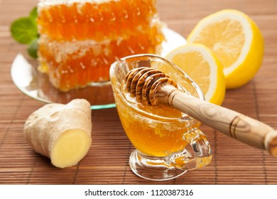 Beautiful composition of honeycombs, ginger, lemon and fresh honey on bamboo background