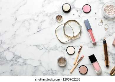 Beautiful composition with lipsticks and bijouterie on marble background, flat lay. Space for text