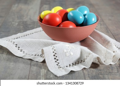 Beautiful composition of multicoloured Easter eggs in a clay bowl on a linen cloth