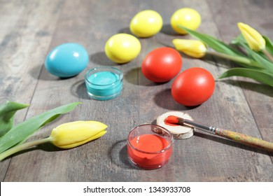 Beautiful composition of multicoloured Easter eggs, spring tulips and painting supplies on a wooden table