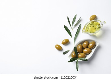 Beautiful composition with oil and ripe olives on white background