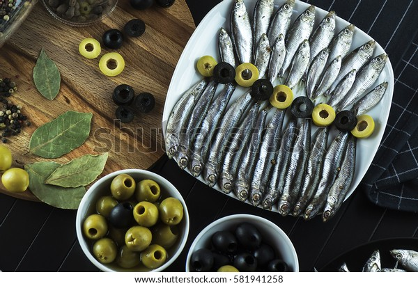 Beautiful composition on the table of the little fish, the anchovy, seasoning and olives