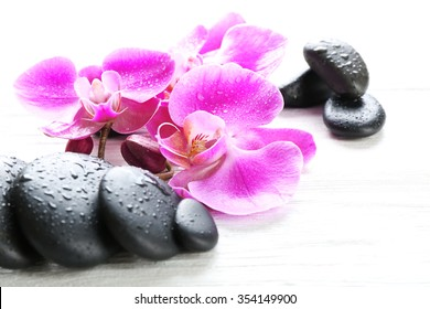 Beautiful composition of orchid and pebbles on white wooden background, close up