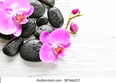 Beautiful composition of orchid and pebbles on white wooden background, copy space