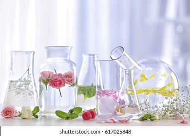 Beautiful composition with perfume samples and flowers on table