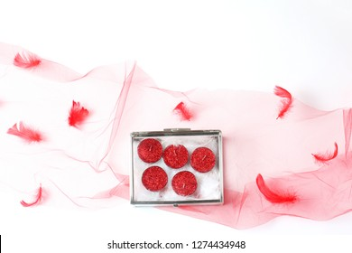 beautiful composition of a red veil and a glass box with candles in glitter. flat lay, top view, creative layout
