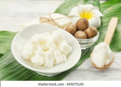 Beautiful composition with shea butter, soap and nuts on wooden table