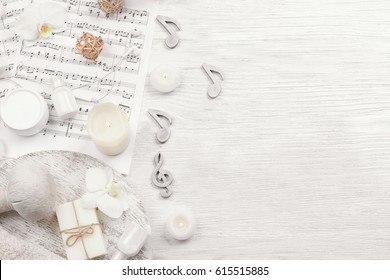 Beautiful composition of spa accessories and musical notes on white wooden background