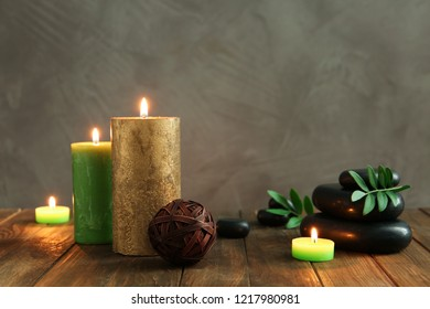 Beautiful composition with spa stones and candles on wooden table. Space for text