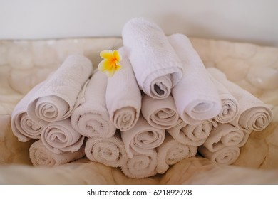 Beautiful composition of spa treatment on wooden table. Pile of white clean towels.