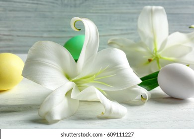 Beautiful composition with white lilies and Easter eggs on wooden background