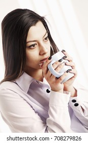 A beautiful, conceived businesswoman enjoying in a cup of coffee at the workplace in the office (coffee breaks, coffee time, break, rest concept)