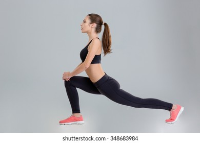 Beautiful concentrated fitness girl in black top and leggings doing stretching exercise over grey background